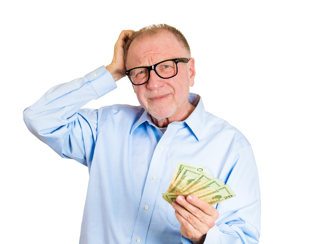 Closeup portrait, nerd senior mature man, black glasses, holding money in one hand, scratching head, not sure how to spend extra cash dollar bills, isolated white background. Human emotion, expression